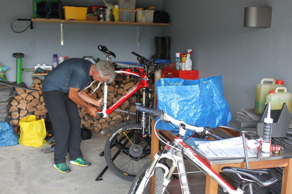 Ospite esegue manutenzione alla sua bicicletta nell'officina del B&B